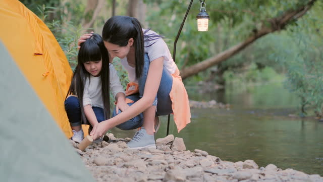asian mother teaching little girl about sustainability in the forest by camping.happy family spending time together outdoor.teaching children about sustainability,family,learning,vacations,relationship,children,holiday - campaigner stock videos & royalty-free footage
