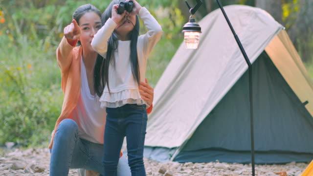 vídeos de stock, filmes e b-roll de mãe asiática ensinando a menina sobre sustentabilidade na floresta e menina animada em uma viagem de acampamento com binóculos em busca de aventuras na floresta verde da natureza. ensinando crianças sobre sustentabilidade - ecossistema