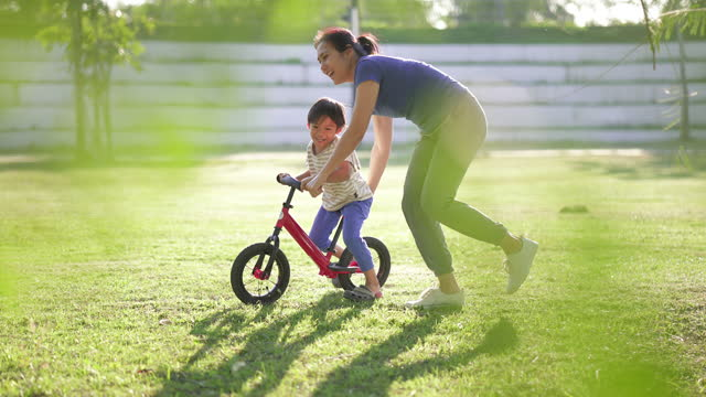 asian mother teaching son to riding a bicycle in park. - single mother stock videos & royalty-free footage