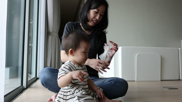 asian mother trying to put decorative headband on for her baby - hair accessory stock videos & royalty-free footage