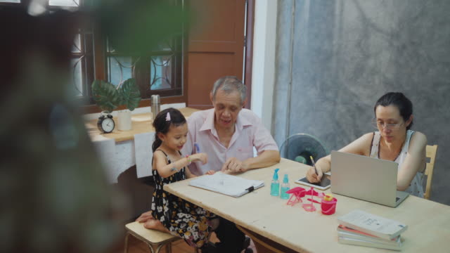 asian mother using computer working from home her daughter playing with grandfather - prevenzione delle malattie video stock e b–roll