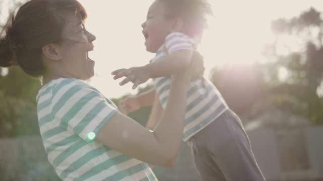 vídeos de stock, filmes e b-roll de asiática mãe com filho na praia - bebês meninos