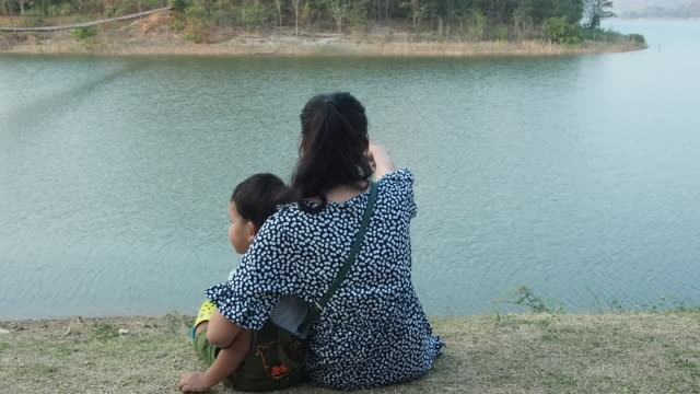 asian mother with children sitting by the river - small stock videos & royalty-free footage