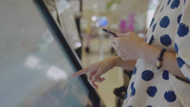 空港での飛行時間を見つける彼女の娘とアジアの母 - 標識点の映像素材/bロール