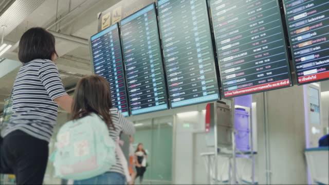 vídeos y material grabado en eventos de stock de asia madre con su hija de encontrar tiempo de vuelo en el aeropuerto - ticket