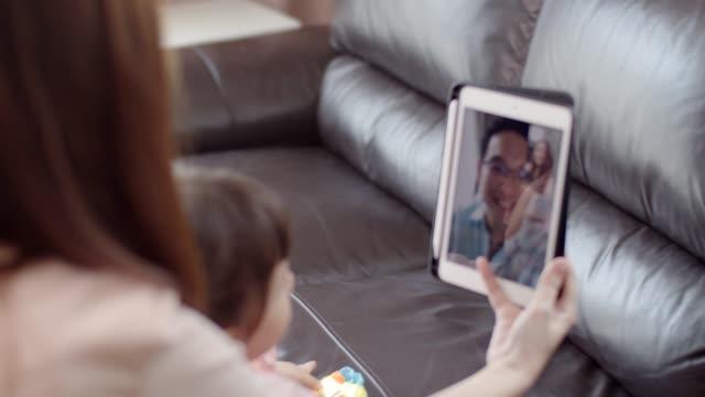 vídeos y material grabado en eventos de stock de madre asiática con hija pequeña haciendo videollamadas a su marido. - familia con un hijo