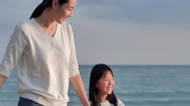 asiatische mutter mit kleinen mädchen zu fuß mit spaß entlang rand des sonnenuntergangs meer surfen auf sandstrand. frohe familienurlaube. urlaub - east asian ethnicity stock-videos und b-roll-filmmaterial