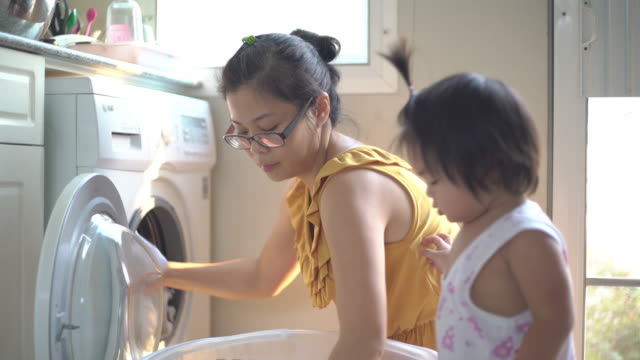 asian mother with son is washing clothes in an automatic laundry at home - tumble dryer stock videos & royalty-free footage
