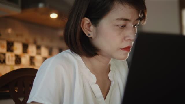 stockvideo's en b-roll-footage met aziatische moeder werkt op laptopcomputer thuis. - e mail