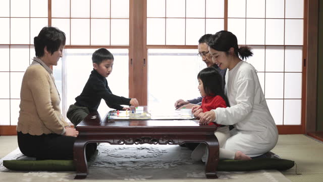 asian multi generation family playing a board game together - board game stock videos & royalty-free footage