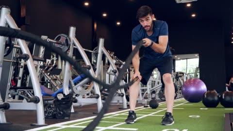 vídeos y material grabado en eventos de stock de mujer musculosa asiática hacer ejercicio en el gimnasio por cuerda. healty, poder, fuerza, estilo de vida, concepto deportivo. metraje a cámara lenta - cuerda