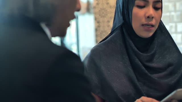 asian muslim business team meeting at a cafe using tablet. business people meeting partnership.business adviser analyzing financial figures of the company while meeting.business people technology and teamwork concept.arab youth - finishing stock videos & royalty-free footage