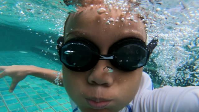 vídeos de stock, filmes e b-roll de as crianças muçulmanas asiáticas a nadar em uma piscina de apartamento - prendendo a respiração