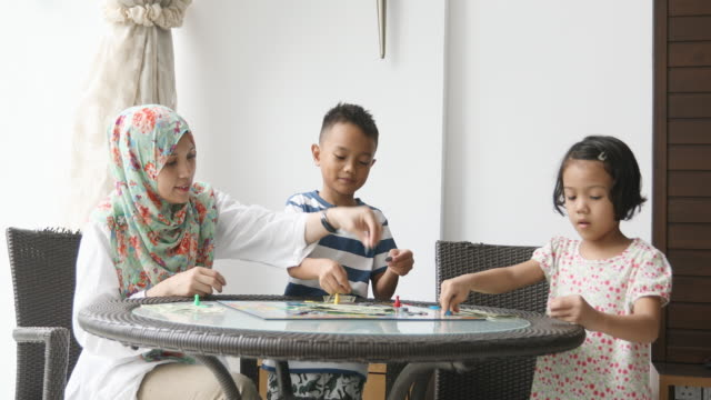 asian muslim family playing a board game together - islam stock videos & royalty-free footage