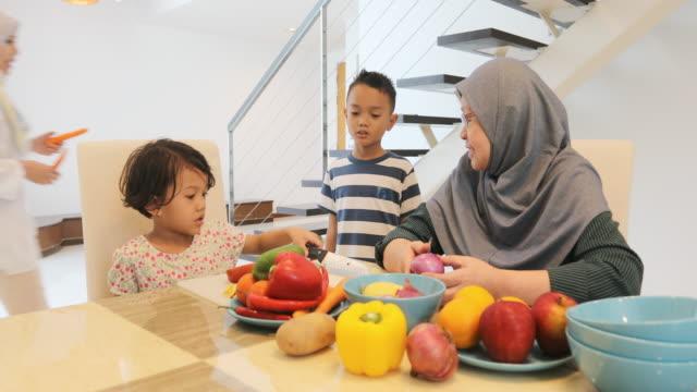 vidéos et rushes de famille musulmane asiatique, préparer un repas ensemble - foulard