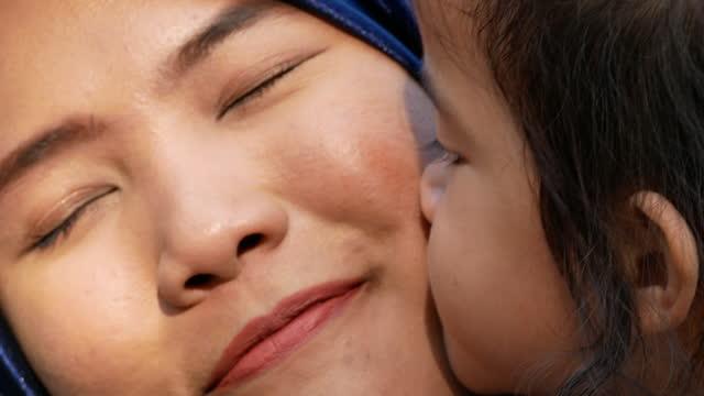 vidéos et rushes de musulman asiatique fanily dans le stationnement, mère et descendant jouant ensemble dans le jardin, fille embrassant la mère - islam