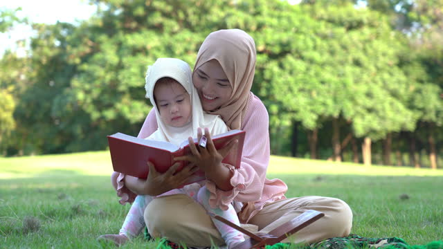 asian muslim fanily in park , mother try to teach daughter spelling holy book and pray in garden - reading stock videos & royalty-free footage