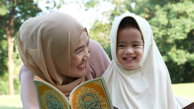 asian muslim fanily in park , mother try to teach daughter spelling holy book and pray in garden - symbol stock videos & royalty-free footage