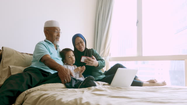 asian muslim grandparents looking at a mobile phone with their granddaughter - cultura malesiana video stock e b–roll