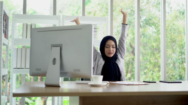 asian muslim lady stretch her body at the office. - relaxation exercise stock videos & royalty-free footage