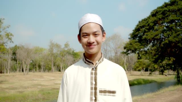 asiatiska muslimska mannen porträtt på thailändska antika tempel och bära hijab.4k slow motion. - från mellanöstern bildbanksvideor och videomaterial från bakom kulisserna