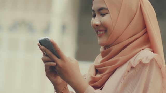 vidéos et rushes de musulman asiatique utilisant le téléphone. connexion - fête religieuse