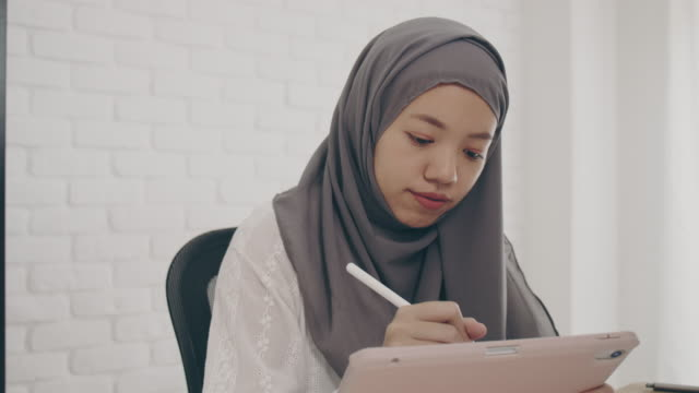 asian muslim woman student or businesswoman waring hijab.working from home with computer and tablet online.concept of social distancing working alone at home in the epidemic situation of covid-19. - beautiful people stock videos & royalty-free footage