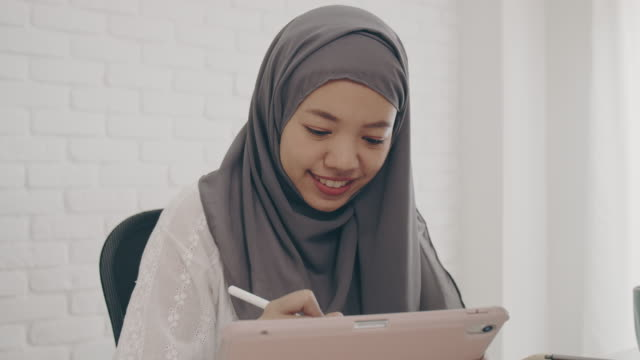 asian muslim woman student or businesswoman waring hijab.working from home with computer and tablet online.concept of social distancing working alone at home in the epidemic situation of covid-19. - hijab stock videos & royalty-free footage