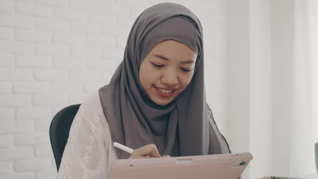vídeos y material grabado en eventos de stock de asiática musulmana estudiante o empresaria guerra hijab. trabajando desde casa con computadora y tablet en línea. concepto de distanciamiento social trabajando solo en casa en la situación epidémica de covid-19. - oriental asiático e indio