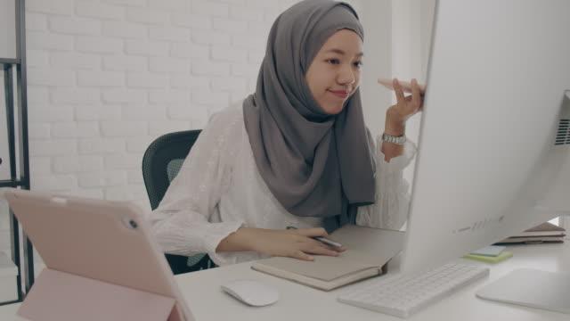vídeos y material grabado en eventos de stock de asiática musulmana estudiante o empresaria guerra hijab. trabajando desde casa con ordenador y smartphone. concepto de distanciamiento social trabajando solo en casa en la situación epidémica de covid-19. - oriental asiático e indio