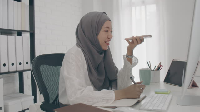 asian muslim woman student or businesswoman waring hijab.working from home with computer and smartphone.concept of social distancing working alone at home in the epidemic situation of covid-19. - hijab stock videos & royalty-free footage