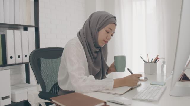 vídeos y material grabado en eventos de stock de asiática musulmana estudiante o empresaria guerra hijab. trabajar desde casa con computadora y escribir nota en papel. bebe café porque tiene sueño. concepto de distanciamiento social trabajando solo en casa en la epidemia de cóvidio-19. - oriental asiático e indio