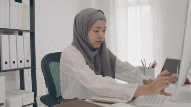 asian muslim woman student or businesswoman waring hijab.working from home with computer and writing note on paper.concept of social distancing working alone at home in the epidemic situation of covid-19. - hijab stock videos & royalty-free footage
