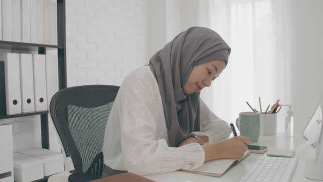 asian muslim woman student or businesswoman waring hijab.working from home with computer and writing note on paper.drink coffee because feel sleepy.concept of social distancing working alone at home in epidemic of covid-19. - hijab stock videos & royalty-free footage