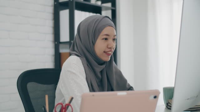 asian muslim woman student or businesswoman waring hijab.working from home with computer and meeting video conference online.concept of social distancing working alone at home in the epidemic situation of covid-19. - video call stock videos & royalty-free footage