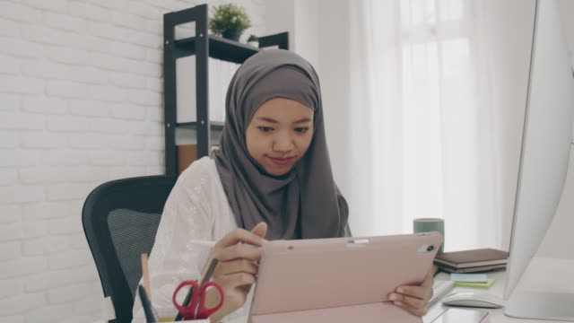 asian muslim woman student or businesswoman waring hijab.working from home with computer and tablet online.concept of social distancing working alone at home in the epidemic situation of covid-19. - young adult stock videos & royalty-free footage
