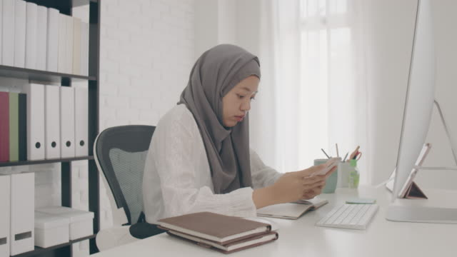 asian muslim woman student or businesswoman waring hijab.working from home work from home with smartphone and computer on table with online news.concept of social distancing to stop the spread disease of corona virus.4k uhd.slow motion. - islam stock videos & royalty-free footage