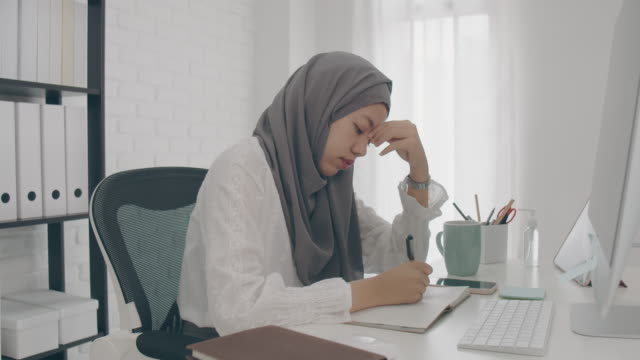 asian muslim woman student or businesswoman waring hijab.working from home with computer and writing note on paper.feeling stress and headache. concept of social distancing working alone at home in epidemic of covid-19. - hijab stock videos & royalty-free footage