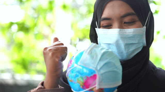 asian muslim woman with surgical mask protection applying alcohol sanitizer on globe model , protect the world from disease or covid-19 concept , cheering and thumbs up for good condition - good condition stock videos & royalty-free footage
