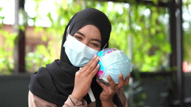 asian muslim woman with surgical mask protection applying alcohol sanitizer on globe model , protect the world from disease or covid-19 concept , cheering and lullaby for support religious spirit , hope concept - rubbing alcohol stock videos & royalty-free footage