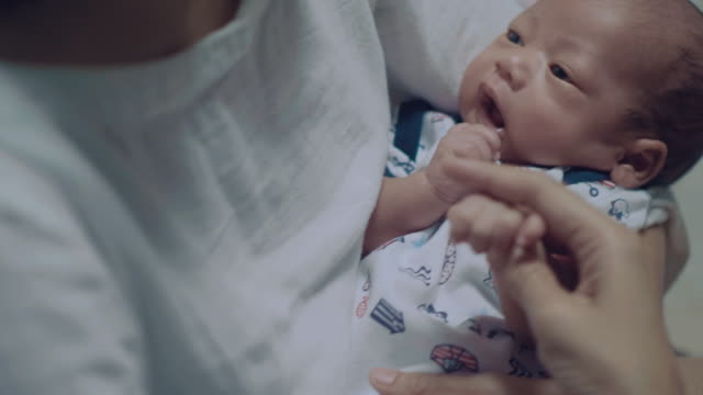 asian newborn baby resting in mother's arm - dondolarsi video stock e b–roll