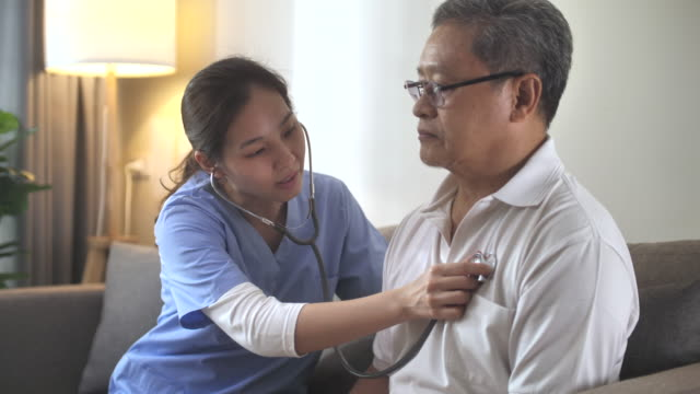 asian nurse checking a senior patient for the stethoscope at home - retirement community stock videos & royalty-free footage
