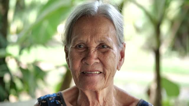 vidéos et rushes de asiatique de vieille femme aux cheveux gris aînée âgée âgée de 83 ans regardant l'appareil-photo. belles femmes âgées joyeuses souriant tout en étant de bonne humeur. grand-mère mûre aînée heureuse avec le sourire toothy à la maison ou à l - new age concept