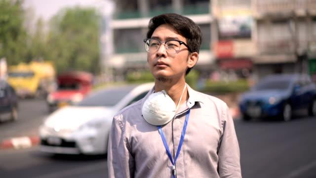屋外通りで大気汚染マスクを着用したアジアのオフィスマンホワイトカラーワーカー - white collar worker点の映像素材/bロール