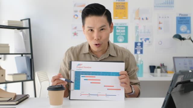 vídeos de stock, filmes e b-roll de pov de vídeo conferência de escritório asiático com laptop em novo escritório normal - apresentador