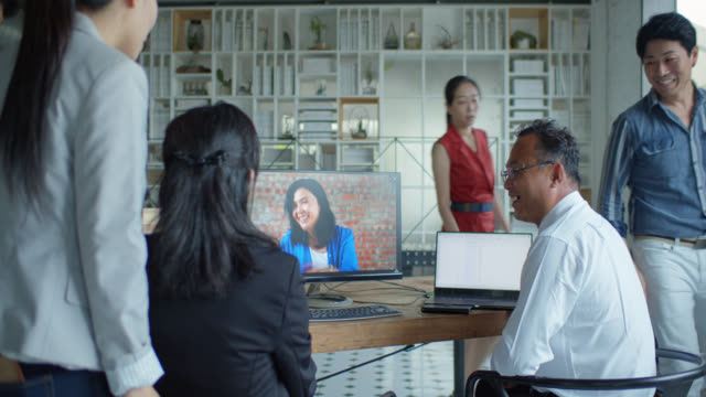 Asian Office Workers Joining Colleagues in Video Conference
