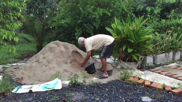 vidéos et rushes de le vieil homme asiatique portent le sable - plateforme