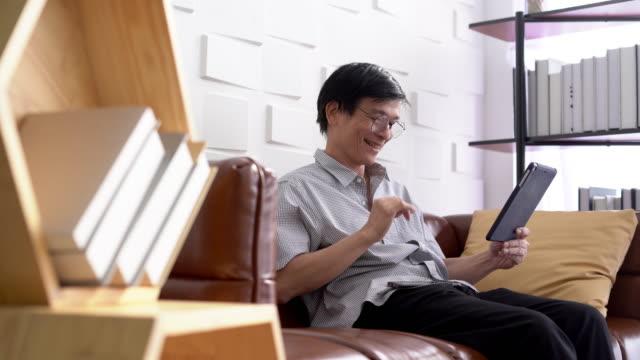 vídeos de stock, filmes e b-roll de chamada de vídeo do homem idoso asiático em uma tabuleta digital em casa - adulto