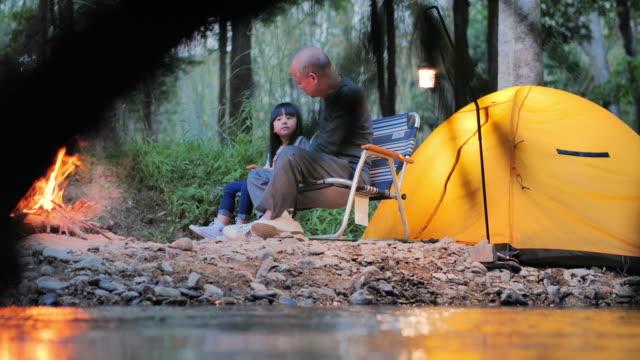 asiatische ältere mann und baby mädchen im gespräch und genießen im camping in der nähe von lagerfeuer auf wald. familie,lifestyle,menschen,mehrgenerationen,ältere,urlaub,beziehung,ruhestand,gesundepflege und medizin konzept.. eine großeltern-liebe - east asian ethnicity stock-videos und b-roll-filmmaterial