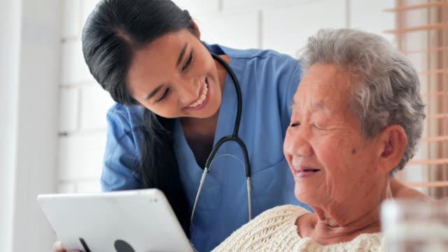 asiatische ältere frau im gespräch mit jungen schwarzen krankenschwester arzt helfen patienten bildung auf tablet zu covid-19 virus medizinisch zu hause. ausbildung,medizin,pflege,technologie,senior care,ruhestand,freiwillige,charity,pflegeheim,coronavir - wiederherstellen stock-videos und b-roll-filmmaterial